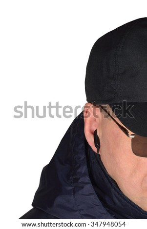 Police security guard specops staff policeman covertly listening isolated portrait agent covert earpiece detailed closeup caucasian vertical cop officer black eyeglasses blue jacket hood baseball cap