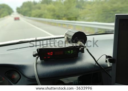 Police speed radar unit in police car driving on 2 lane road. - stock photo