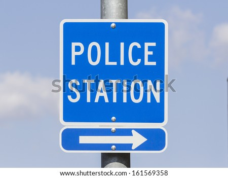 Police Station direction sign with blue sky. - stock photo