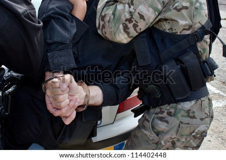 police task force arrested a dangerous criminal, handcuffed hands - stock photo