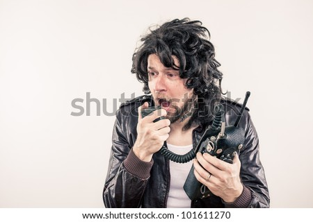 Police undercover narc on radio freaking out during emergency with greasy hair - stock photo