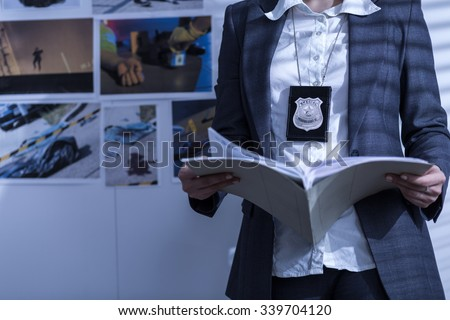 Police woman is reviewing files and documents - stock photo