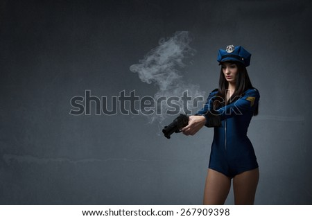 police woman shot with gun, dark and empty background - stock photo