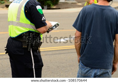 Police writing a citation at a four vehicle accident involving two large trucks resulted in a single injury and a diesel fuel spill. July 17, 2012 in Roseburg Oregon - stock photo