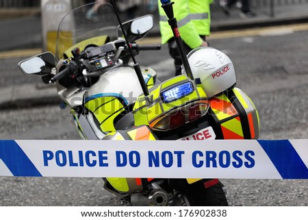 Policeman and police motorcycle behind cordon tape at an accident or crime scene - stock photo