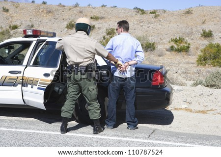 Policeman arresting somebody - stock photo