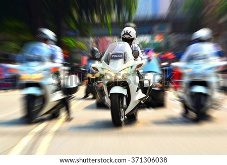 Policeman on motorcycle escorting government officials - stock photo