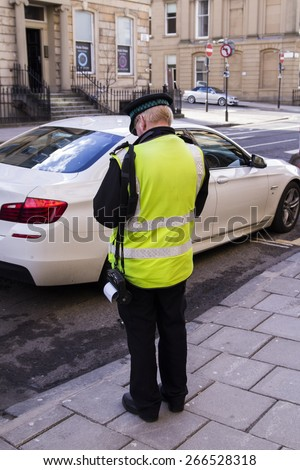 POLICEMAN,SHOT FROM BACK, GIVING A TICKET FOR BAD PARKING OR NOT PAYING TAX ,IN A SUNNY DAY IN STREETS OF UK - stock photo