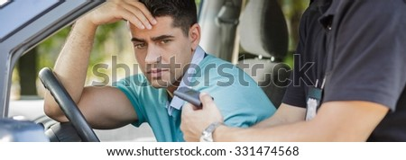 Policeman wants male driver to take breathalyzer test - stock photo
