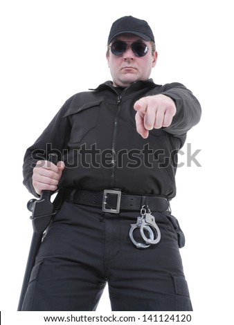 Policeman wearing black uniform and glasses pointing in ordering manner - stock photo