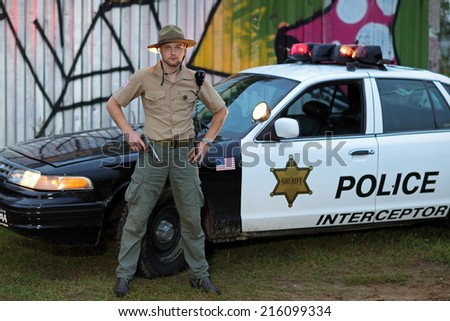 Policeman with a gun standing beside his car - stock photo