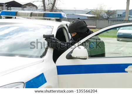 policeman with a gun to cover for car - stock photo