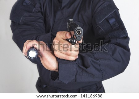 Policeman with gun and flashlight - stock photo
