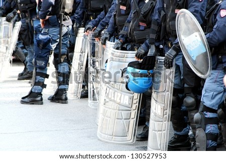 policemen in riot gear with shields and helmets and helmets during the urban riots
