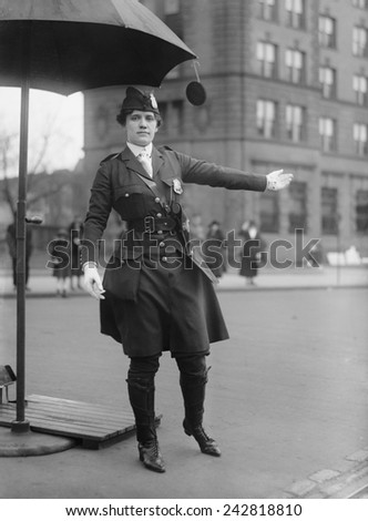 Policewoman directing traffic in Washington, D.C. in 1918. Her progressive uniform combines knee high boots, below knee pants, and a knee length jacket. - stock photo