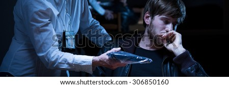Policewoman showing suspected man evidence of crime - stock photo