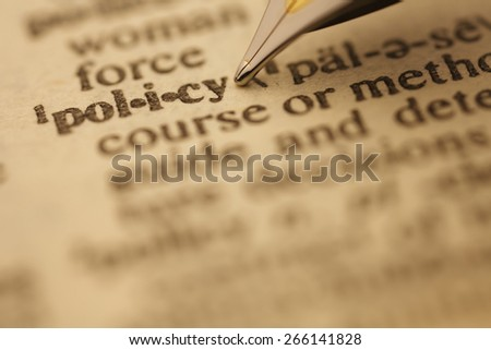 policy pen nib pointing to the words in the dictionary, shot with very shallow depth of field,