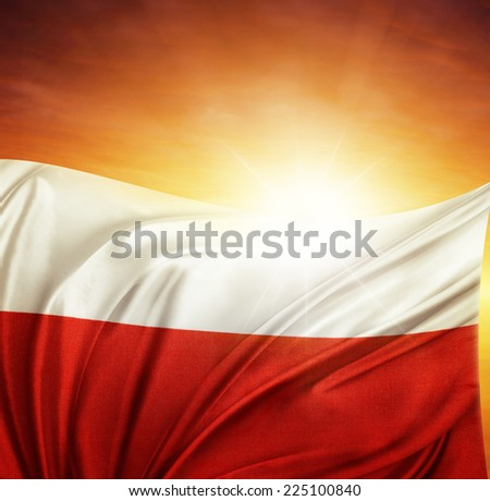Polish flag in front of bright sky - stock photo