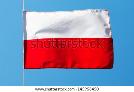 Polish flag in wind against the sky - stock photo