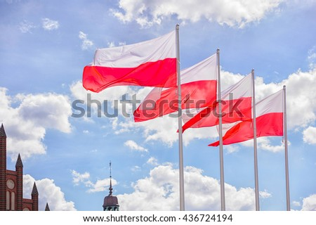 Polish flags are waving on the wind  against bright sky