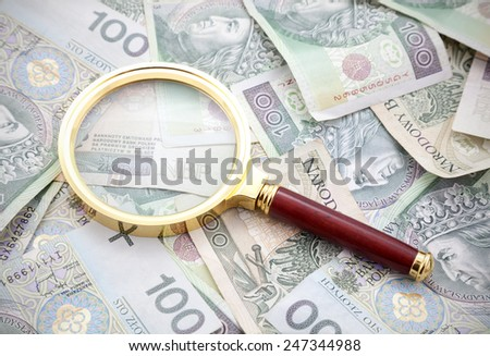 Polish money with golden magnifying glass - stock photo