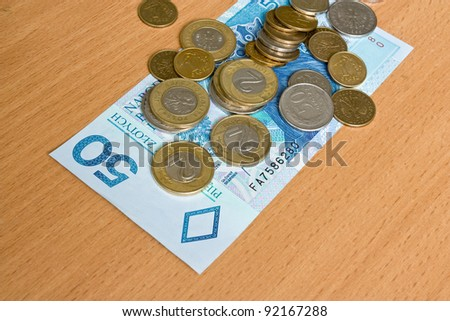 polish money - zloty, banknotes and coins on the table - stock photo