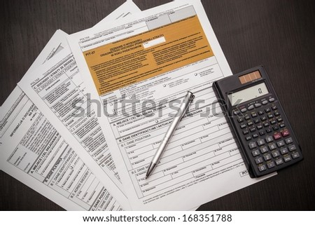 Polish tax form with pen and calculator on desk - stock photo