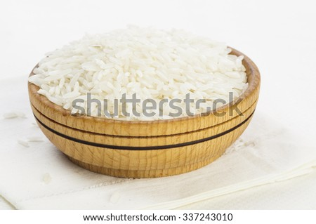 Polished long rice in wooden bowl isolated on white background - stock photo