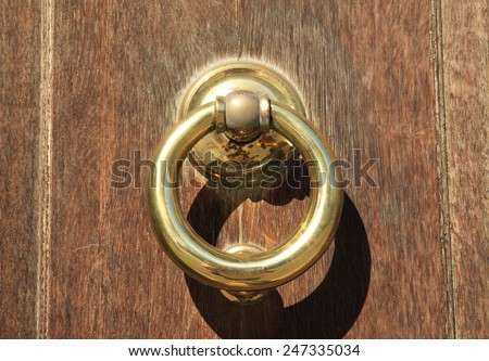 Polished old heavy brass door knocker - stock photo