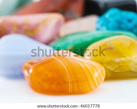 Polished orange striped agate gemstone in front of gemstone collection - stock photo