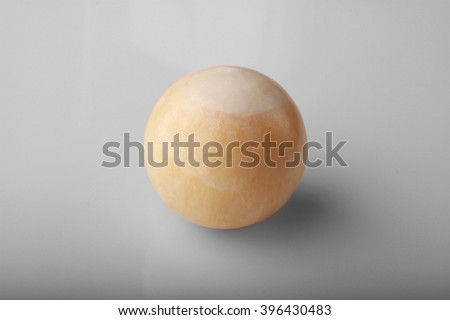 Polished round stone yellow calcite on a gray background.