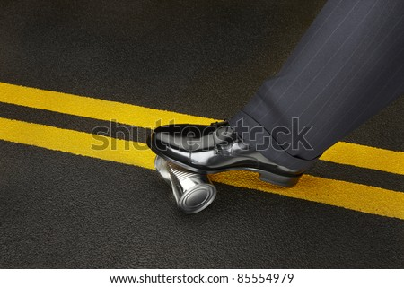 Politician's shoe stops a dented can from rolling on a road - stock photo