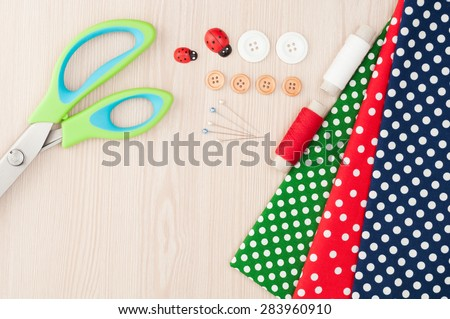 Polka dot fabric for sewing and accessories for needlework on wooden background. Spool of thread, scissors, buttons, sewing supplies. Set for needlework top view - stock photo