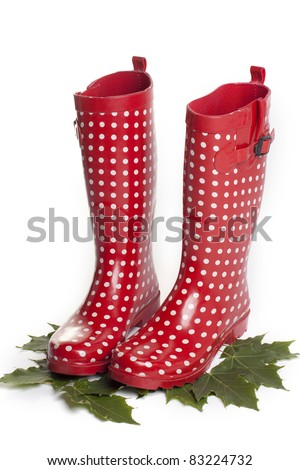 Polka dot red rain boots with autumn leaves on white background - stock photo