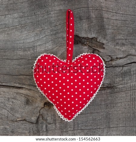 Polka dotted heart shape hanging on a wooden background for Valentine, birthday or christmas with polka dots