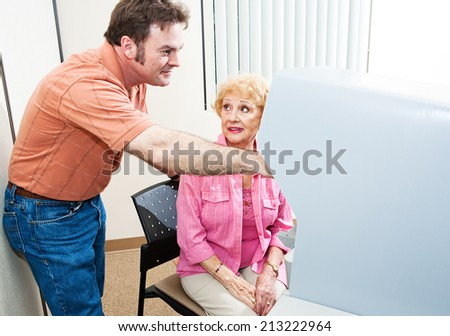 Poll worker helping senior woman who is confused by touch screen voting machine.   - stock photo