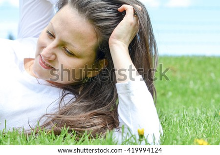 Pollen allergy -  pretty girl laying in the grass - stock photo