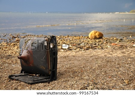 Polluted Baltic sea shore and old TV set - stock photo
