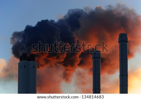 Pollution concept of smoking chimneys. The setting sun illuminates the vapor from below, giving it an ominous impression, like that of volcano smoke.