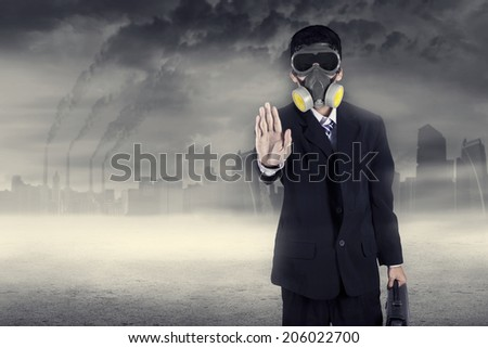 Pollution concept: portrait of businessman in a gas mask warn to stop pollution - stock photo