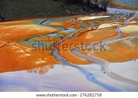 Pollution of a lake with contaminated water from a gold mine  - stock photo