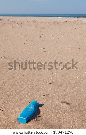 Pollution - Plastic Can on beach - stock photo