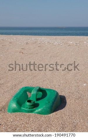 Pollution - Plastic Jerry can on sand. - stock photo