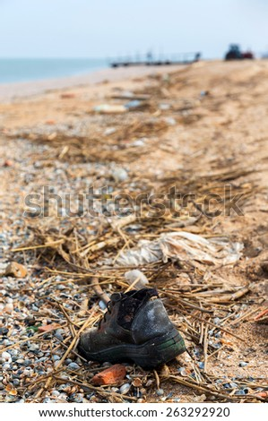 Pollution: shoes,  garbages, plastic, and wastes on the beach after winter storms. Azov sea. dolganka - stock photo