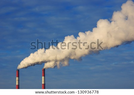 Pollution. Smoke from industrial chimneys against the blue sky - stock photo