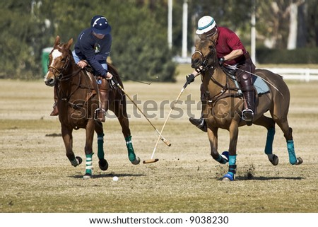 Polo players cross mallets in a practice chukker