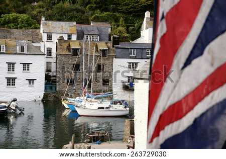 POLPERRO, UK - AUGUST 21, 2013: View across the small harbor in  the tiny fishing village of Polperro, Cornwall, which serves as a major tourist destination during English Summer Holidays. - stock photo
