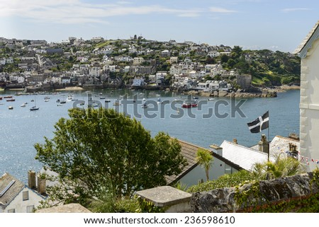 Polruan and cove from Fowey, Cornwall, view of cove harbor and village on southern coast of Cornwall, shot from the opposite side of the cove whit a flag in foreground  - stock photo