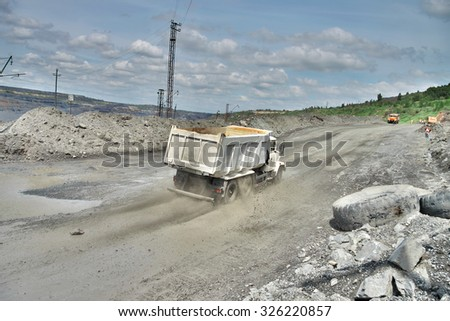 Poltava Region, Ukraine - June 26, 2010: Dump trucks on the iron ore opencast