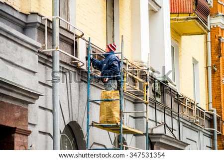 POLTAVA, UKRAINE - DECEMBER 5, 2015 : An unidentified workers repair front part of building construction in the center of Poltava.
